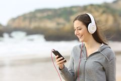 Teenage girl listening to music on the beach. Happy teenage girl listening to music with headphones and a smart phone on the beach Royalty Free Stock Photo