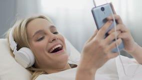 Teenage girl listening to music in headphones, watching online video, closeup. Stock footage stock video footage