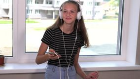 Teenage girl listening to music on her mobile. Phone standing in front of a windowing smiling and singing along to the music stock video