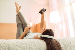 Teenage girl listening to music and looking at player. Enjoying music. Pretty teenage girl lying on her bed and looking at a player while listening to the music Stock Photos