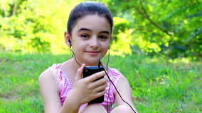 Teenage girl listening to music on a smart phone stock video footage