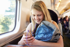 Teenage Girl Listening To Music On Train Journey royalty free stock photo