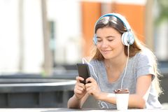 Teenage girl listening to music using phone in a park royalty free stock photography
