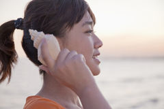 Teenage girl listening to seashell, profile Royalty Free Stock Photos