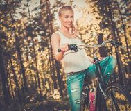 Teenage girl listens music on a bicycle outdoors Stock Photo