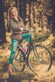 Teenage girl listens music on a bicycle outdoors Royalty Free Stock Photography