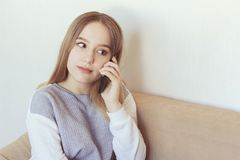 Teenage girl holding the phone. A teenage girl listens to her phone calls and smiles Royalty Free Stock Photo