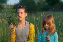 Teenage girl and little girl smelling flowers Royalty Free Stock Photography