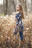 A teenage girl with long brown hair and a blue plaid shirt standing in forest in autumn. Stock Images