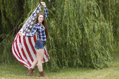 A teenage girl with long brown hair holding an American flag scarf. Stock Photos
