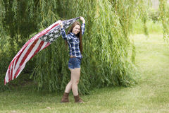 A teenage girl with long brown hair holding a flag scarf. Royalty Free Stock Photo