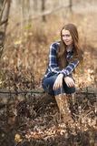 A teenage girl with long brown hair and plaid shirt sitting on log in woods. Stock Photos