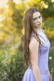 A teenage girl with long brown hair standing sideways in summer grasses. Stock Photography