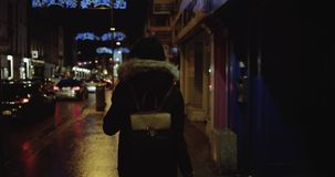 Teenage girl with long brunette hair walking fast along the street,listening to the music,wearing headphones at night stock footage