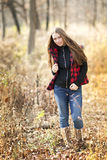Teenage girl with long flowing hair in the woods with plaid vest. Royalty Free Stock Photo
