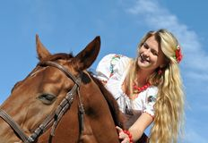 Teenage girl with long hair horseback riding. In sunny day stock photo