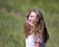 Teenage Girl with Long Hair Laughs in the Sunshine Royalty Free Stock Photo