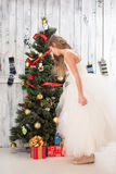 Teenage girl looking at Christmas present near New Year tree Royalty Free Stock Photography