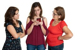 Teenage girl looking at her cellphone while her worried mother and grandmother look at her. Teenage girl looking at her cellphone while her mother and royalty free stock photos