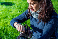 Teenage girl looking at her hand watch. And sitting on green grass Stock Images