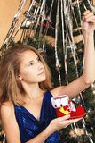 Teenage girl looking at jewelry in the hand, extracted from the Shoe Santa. Beautiful teen girl near christmas tree happily looks at jewelery in her hands Stock Photography