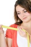 Teenage girl looking at measuring tape Royalty Free Stock Photos