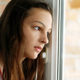 Teenage girl looking out  window Royalty Free Stock Image