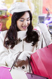 Teenage girl looking at shopping bags at mall Royalty Free Stock Image