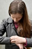 Timecheck, girl controls time on her wristwatch. A teenage girl looks on her wristwatch and checks the time Stock Photo