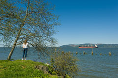 Teenage Girl looks out at Ship in the Columbia River. A teenage girl stands along the banks of the Columbia River in Astoria, Oregon looking at a passing royalty free stock photography