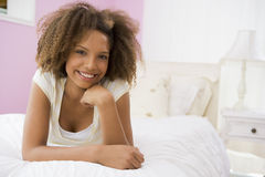 Teenage Girl Lying On Bed Stock Photo