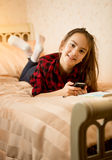 Teenage girl lying on bed and typing message Stock Photography