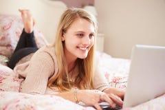 Teenage Girl Lying On Bed Using Laptop Stock Images