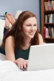 Teenage Girl Lying On Bed Using Laptop Stock Photos