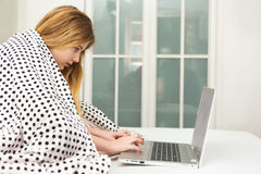 Teenage girl lying on bed using laptop, Royalty Free Stock Photography
