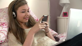 Teenage Girl Lying On Bed Using Laptop Whilst Texting stock video footage