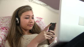 Teenage Girl Lying On Bed Using Laptop Whilst Texting Royalty Free Stock Images