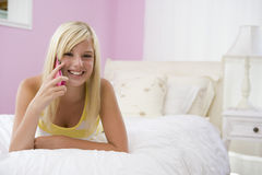 Teenage Girl Lying On Bed Using Mobile Phone Royalty Free Stock Photos