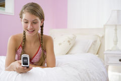 Teenage Girl Lying On Bed Using Mobile Phone Stock Photo