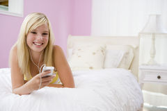 Teenage Girl Lying On Bed Using Mp3 Player Royalty Free Stock Image
