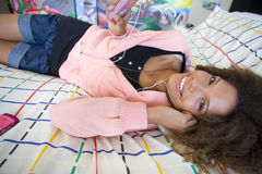 Teenage girl (16-18) lying on bed wearing earphones and holding mp3 player, smiling, portrait, close-up Royalty Free Stock Photography
