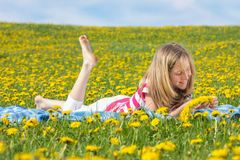 Teenage girl lying on a dandelion field Stock Photos