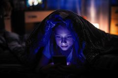 Teenage girl lying in the dark under a blanket looking at the smartphone. Playing. Teenage girl lying in the dark under a blanket looking at the smartphone royalty free stock photos