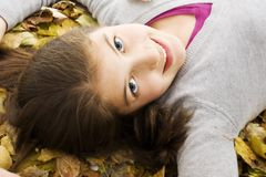 Teenage girl lying down with leaves around. Royalty Free Stock Photography