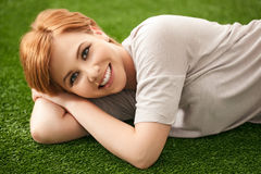 Teenage Girl Lying on Floor. Beautiful smiling red-haired teenage girl lying on a grass-like carpet royalty free stock photos