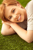 Teenage Girl Lying on Floor. Beautiful smiling red-haired teenage girl lying on a grass-like carpet stock images