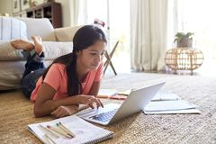 Teenage girl lying on the floor in the living room doing her homework using a laptop computer, low angle, close up stock photo