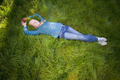 Teenage girl (11-13) lying in grass with eyes closed, elevated view (full frame) royalty free stock photos