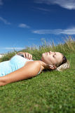 Teenage girl lying on grass with mp3 player Royalty Free Stock Images