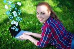 Teenage girl lying on grass in park and using laptop with differ Stock Photography